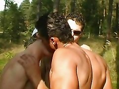 Three studs having a group sex outdoor