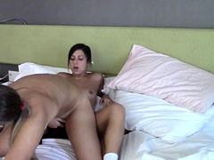 Sweet lesbian friends play with a strap-on dildo on the bed