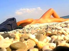 Nudist beach voyeur finds a sexy brunette enjoying the sun