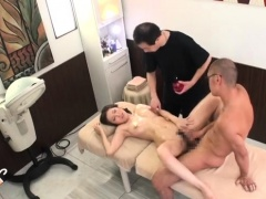 Gorgeous Japanese babe enjoys two cocks on the massage bed