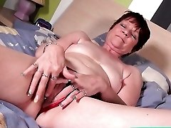 Mature model in shiny red high heels masturbates