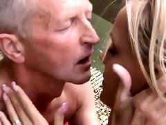 Old and young girl massage Naked on a bridge in a public par