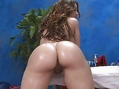 Oiled brunette taking it anal